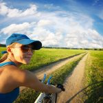 19362672 - young smiling lady cycling on a countryside road at summer sunny day